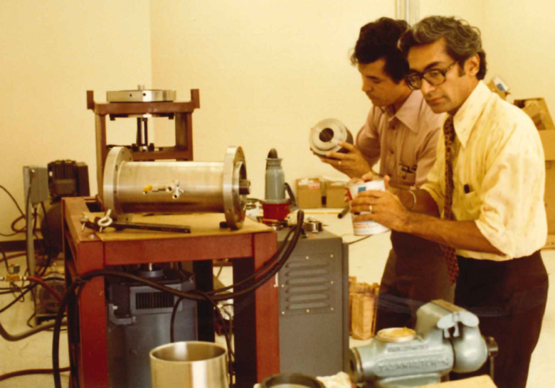 In this 1981 photo, Dr. Kalsi (right) and Daniel Alvarez are part way through the process of assembling Kalsi Engineering's first seal test fixture. The laboratory was a small rented storefront. This fixture was used to develop and characterize our first commercially successful rotary sealing product.
