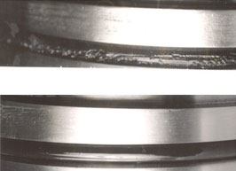 The seal on the top was tested in a circular groove and was severely damaged. The seal on the bottom was tested in a slanted groove that was designed to promote hydrodynamic lubrication and was undamaged.